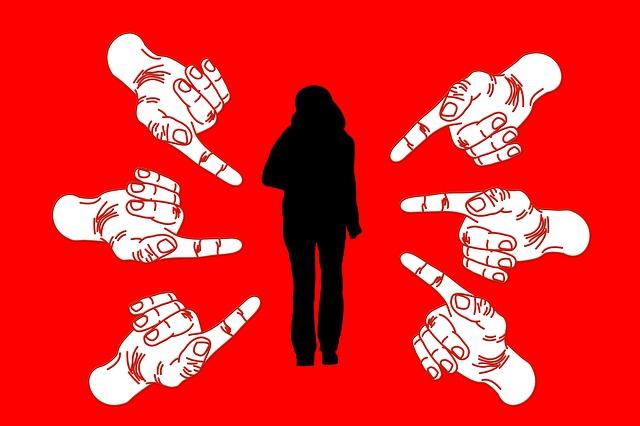 stojící žena a na ní ukazující prsty ze všech stran