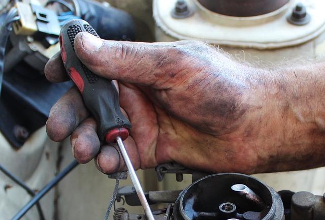ruka tmavá zašpiněná od šmíru drží šroubovák