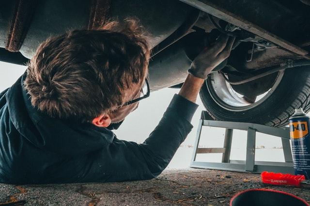 muž s brýlemi leží pod automobilem a opravuje něco na podvozku